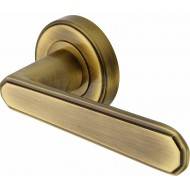Century Deco Lever Handles on Rose in Antique Brass